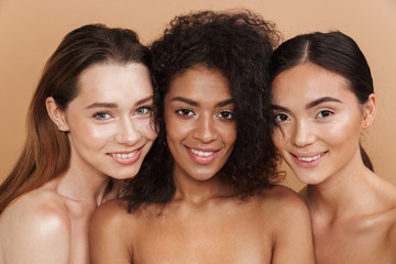Close up image of three happy naked women posing together