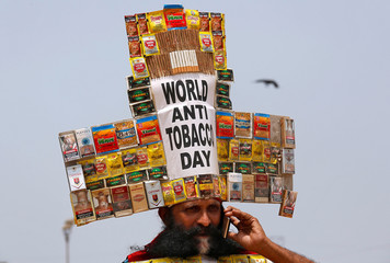 "Rajendra Kumar Tiwari, a social activist, wearing a headgear made from empty cigarettes packets speaks on his mobile phone as he conducts an anti-tobacco awareness campaign to mark ""World No Tobacco Day"" in Mumbai"