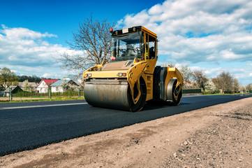yellow road roller makes new asphalt