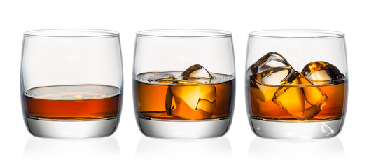 Fototapete - Whiskey in three glasses with ice on a white background
