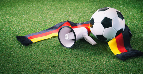Soccer ball with german fan scarf and megaphone