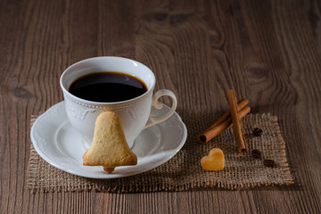 a cup of coffee and cookies like bell and heart with cinnamon, coffee beans on wooden table