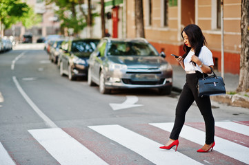 Stylish african american business woman on streets of city at pedestrian crossing.