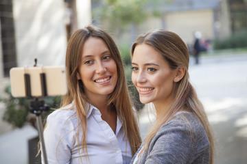Two smiling girls having fun and taking selfie on urban background