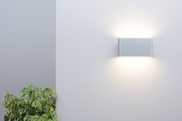 Modern wall lamp on a light wall. Free space and decor in the interior