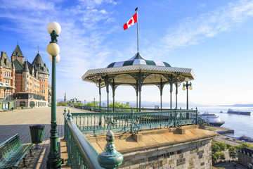 Quebec City, Canada. Early morning shot of Terrasse Dufferin with the Hotel Chateau Frontenac in the background to the left. No people present. A cruise ship at the pier below at Saint Lawrence river.