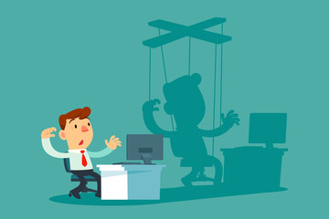 businessman at office desk and his shadow as puppet