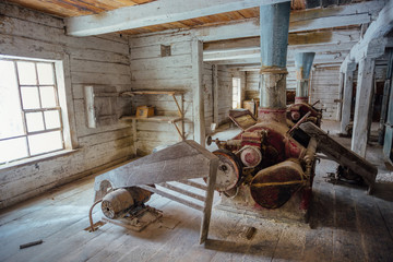 Inside old abandoned wooden mill with old equipment