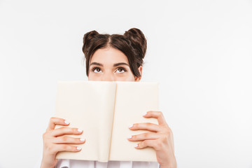 Photo of dreaming teenage girl with double buns hairstyle reading and looking upward while covering face with book, isolated over white background