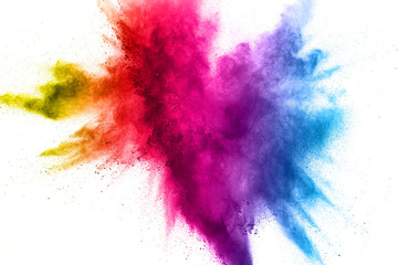 Multi color powder explosion on white background. Bizarre forms of  colorful dust particles splash on dark background.