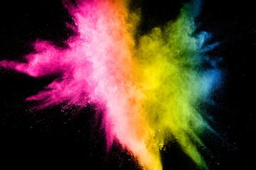Multi color powder explosion on black background. Launched colorful dust particles splash.