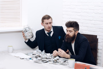 Cash issues concept. Manager with beard and colleague with jar of cash and card. Colleagues collecting money in jar instead of bank account. Business partners, businessmen at meeting in office