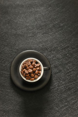 Cup of coffee beans isolated on black