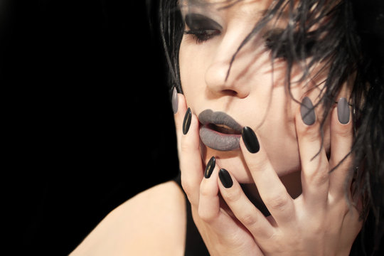 Glamorous matte black gray makeup, and manicures on a sharply oval-shaped nails with feathers of a model on a black  background.