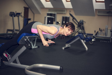 fitness exercises, a woman performs an exercise bar bench press on the shoulders