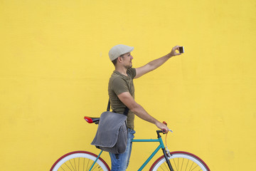 Trendy man taking a selfie with his fixed bike