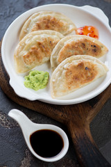 Close-up of fried korean potstickers with dipping sauces, vertical shot, selective focus