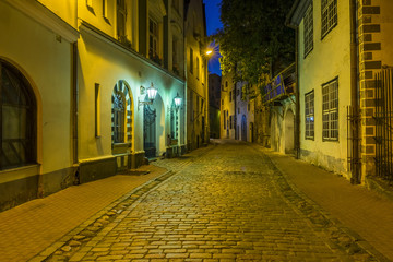 Medieval street by night in old Riga, Latvia, Europe. In old Riga tourists can find unique medieval architectural ensembles and ancient buildings