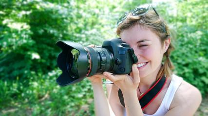 Junges Mädchen mit Profi-Kamera, lächelnd, Fotografin