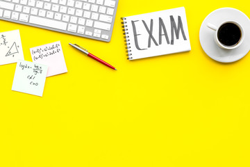 Preparing for the exam. Word Exam written in notebook on student's desk with computer, cup of coffee, cheat sheets on yellow backgrond top view space for text