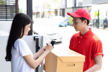 Friendly young delivery person in red uniform holding cardboard box send to customer appending signature electronic receipt after,Delivery concept, Service concept.