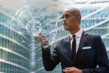 A business man looks at holographic and futuristic graphic on the performance of economic markets and banks. Concept of: success, future and tea