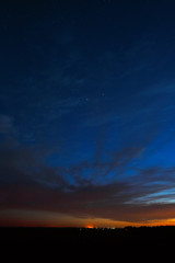 Night sky with stars. A bright sunset with clouds. Cosmic space above the earth's surface. Long exposure.