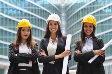 Three engineer women of different ethnicities (Asian, European and African American) with helmets watch a construction project and discuss how to continue the work. Concept of: construction, team