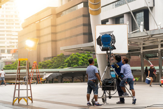 Behind the scene of silhouette film crew team shooting video commercial production. While the crew team is preparing the equipment for filming.