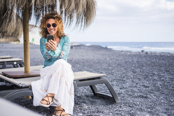 nice smile beautiful middle age lonely woman enjoy the beach sitting on a seat with ocean in background. using smartphone to connect with friends at home or to work with a team online business.