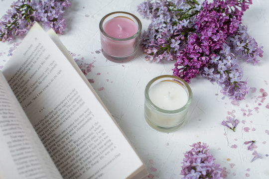 Romantic reading of the book on the background of candles and fresh lilac flowers