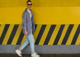 fashion guy standing near a yellow wall in striped clothing