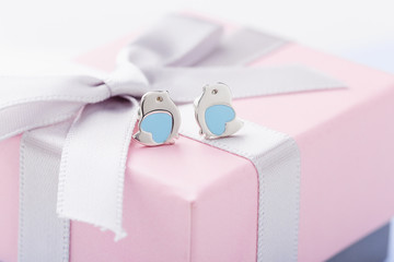 Bird shape with blue heart earring studs pink gift box with bow as background