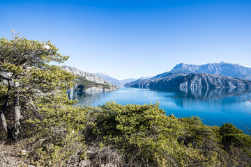 A view of the mountains near lake Lac de serre-poncon in French Alps on a clear day