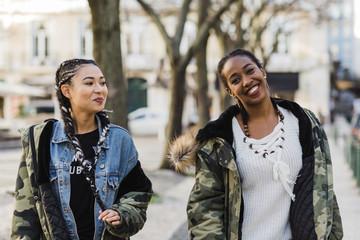 Two smiling young women walking outdoors