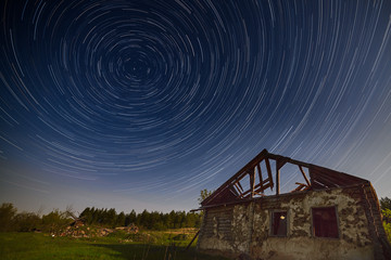 A trail of stars in the night sky over the ruined house. Photographed on a long exposure to the light of the moon.