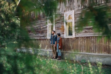 couple near old wooden house