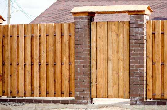Fragment of a wooden brown modern fence with a wicket, close-up. Modern design ideas of a wooden fence.