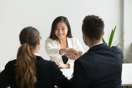Happy millennial asian applicant getting hired shaking hand of hr, employer handshaking successful smiling chinese candidate congratulating with job interview win offering employment contract concept