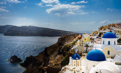 Oia town on Santorini island, Greece. Traditional and famous houses and churches with blue domes over the Caldera, Aegean sea at sunny day