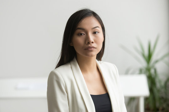 Confident attractive asian businesswoman looking at camera, ambitious serious chinese businesslady posing in office, successful young independent woman business owner head shot portrait