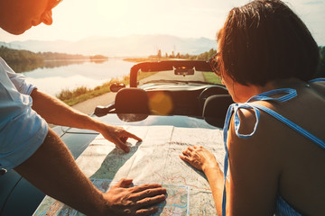 Couple auto travelers plans itinerary with map