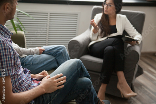 Asian psychologist counseling talking to unhappy couple in