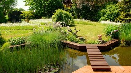 malerischer naturbelassener Garten mit Teich an roter Terrasse mit Holzbrücke und Blumeninseln