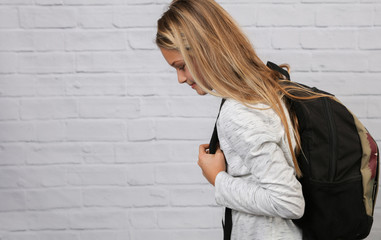 Portrait of schoolgirl wearing heavy backpack, bad posture