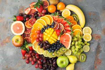 Healthy fruits background in rainbow colours oranges apples grapes pears mango strawberries kiwis on the grey concrete table, top view, copy space, selective focus