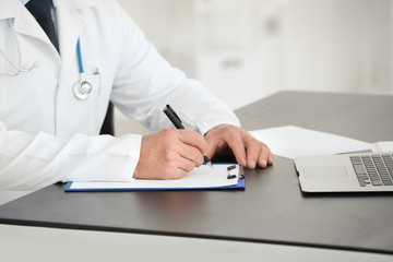 Male doctor filling up application form in consultation room, closeup
