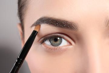 Young woman correcting eyebrow shape with brush, closeup