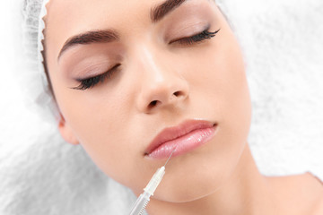 Young woman getting lip injection in beautician salon, closeup