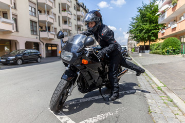 A woman gets on a black motorcycle